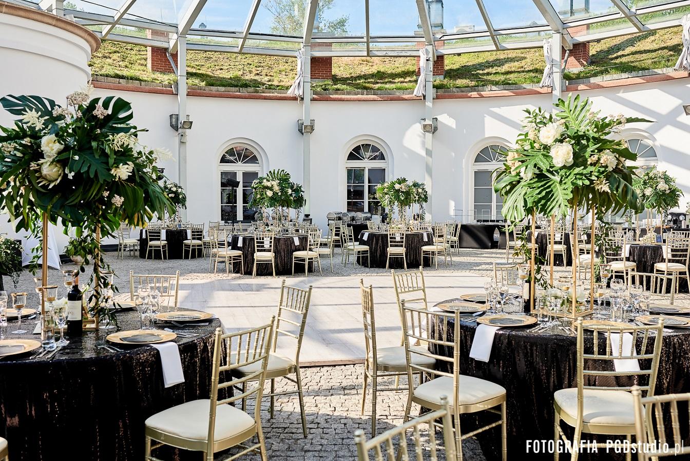 Wesele w motywie art deco the great gatsby organizowane przez Dariusz Zwadowski konsultant ślubny. Na zdjęciu czarny cekinowy obrus, złote podtalerze, świece z złotą obwolutą, papeteria w kształcie sześcianu oraz duży bukiet z liści monstery i białych kwiatów